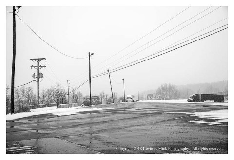 BW photograph of a parking lot during a snowfall.