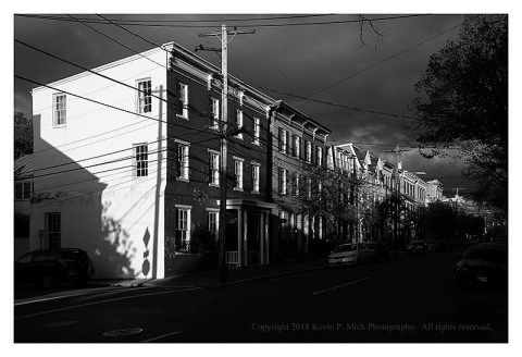 BW photograph looking down a street of row homes the morning after a rain.