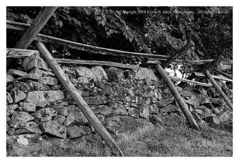BW photograph of a rail fence and stone wall on Culp's Hill.
