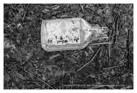 BW photograph of a broken plastic bottle laying on top of the dirt.