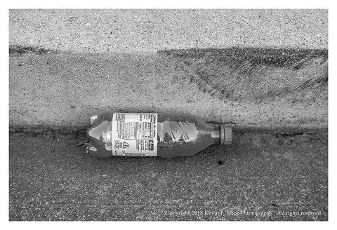 BW photograph of a mostly full plastic soda bottle laying in a gutter.