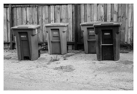 BW photograph of several trash/recycling bins.