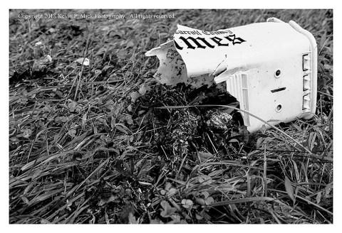BW photograph of a broken mailbox after a flood.
