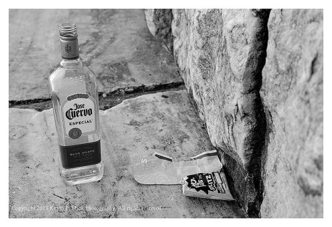 BW photograph of an empty Cuervo bottle and a Pop Tart wrapper sitting on a granite step.