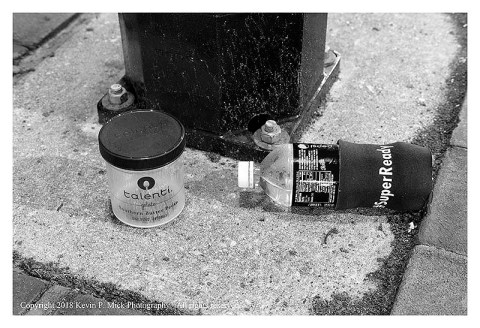 Bw photograph of an empty gelato bin and a Pepsi Bottle laying at the base of a street lamp.