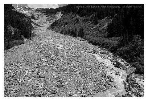 BW photograph of the Nisqually Glacier path with the low flow of the Nisqually River.