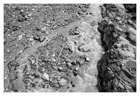 BW photograph of the Nisqually Glacier path with the low flow of the Nisqually River-looking into the river from above.