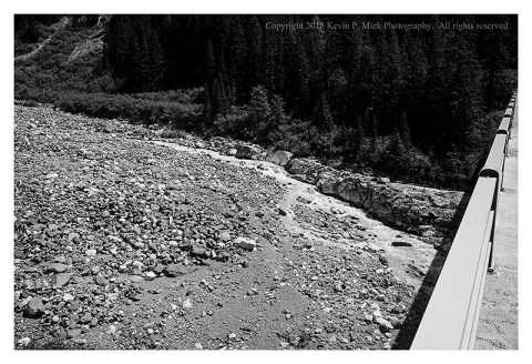 BW photograph of the Nisqually Glacier path with the low flow of the Nisqually River-the bridge is to the right.