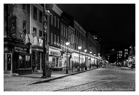 BW photograph looking west down Thames Street before sunrise.