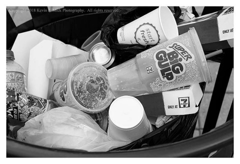 BW photograph of many cups and bottles in a trash can.