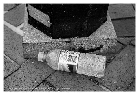 BW photograph of a partially full water bottle laying at the base of a street light.