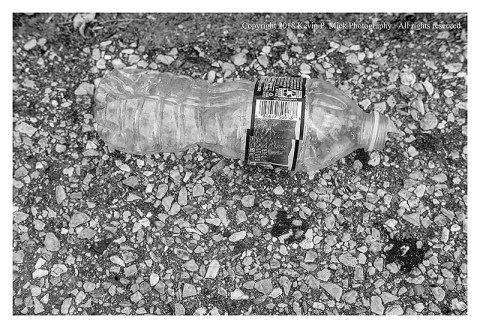 BW photograph of a water bottle laying in the gutter.
