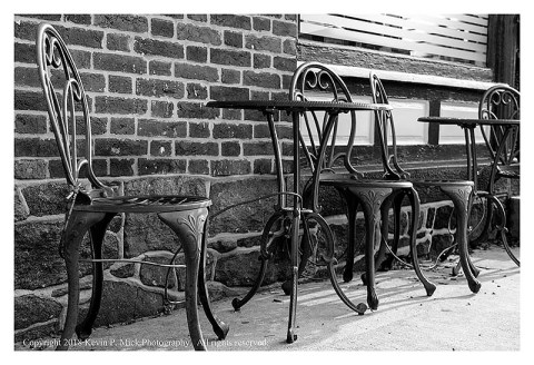 BW photograph of wrought iron chairs and tables.