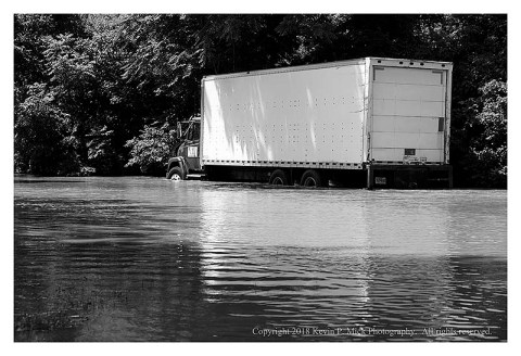 BW photograph of Detour showing the elevated water level of Double Pipe Creek-a moving truck has water to the two-thirds wheel height.