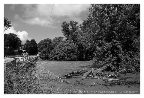 BW photograph of Detour showing the elevated water level of Double Pipe Creek-debris and a flooded fence are in the foreground.