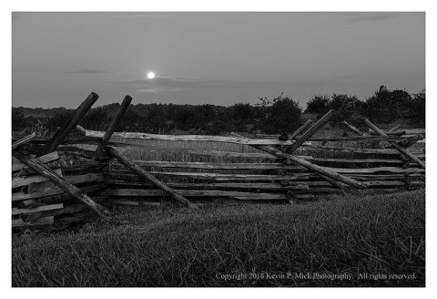 BW photograph of the moon setting over a picket fence.