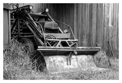 BW photograph of an old Ford tractor with a front end loader.