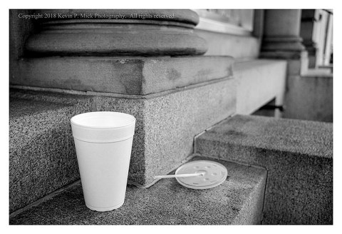 BW photograph of a Styrofoam cup and plastic lid and straw on some steps.