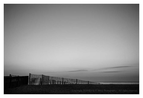 BW photograph of the pre sun rising over the ocean with a dune fence in the foreground.