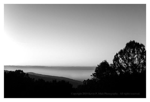 BW photograph of a foggy sunrise looking out from Hog Rock.