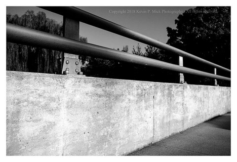 BW photograph of an overpass wall and rail.
