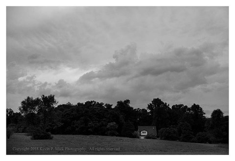 BW photograph of post-thunderstorm clouds over a meadow, treeline, and house.