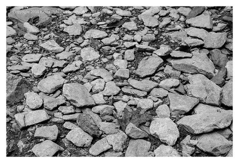BW photograph of the loose rocks on a hiking trail looking up the trail.