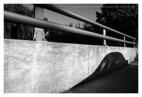 BW photograph of a car's shadow on an overpass wall.