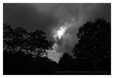 BW photograph of clouds during a thunderstorm with trees in the foreground.