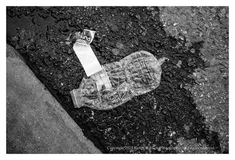 BW photograph of a crushed plastic water bottle laying in the street.