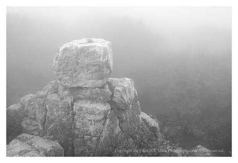BW photograph of Chimney Rock enveloped in fog.