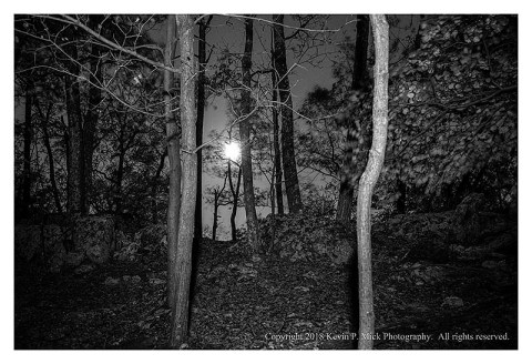 BW photograph of a light-painted scene with the full moon in the background.