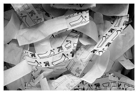 BW photograph of a box of empty bandaid wrappers.