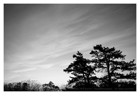 BW photograph of a sunrise looking out from Wolf Rock.