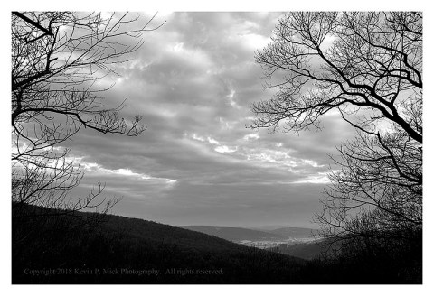 BW photograph of an overlook into a valley between two trees.
