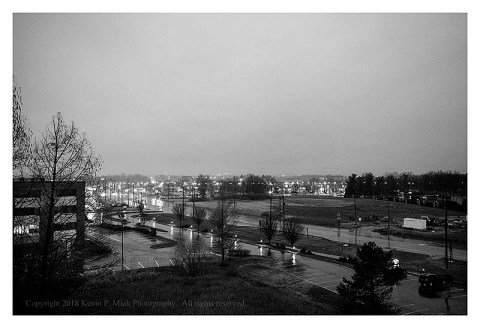 BW photograph looking out over traffic on a rainy evening from a sixth floor hotel window.