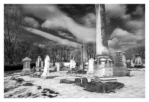 BW photograph of a cemetary with a disused silo in the background.