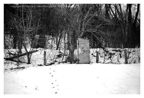 BW photograph of an old outhouse against a background of trees.