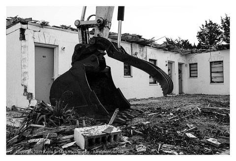 BW photograph showing the bucket of the crane this is being used to demolish the Sands Motel.