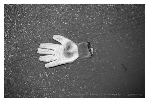 BW photograph of a worn work glove laying in a puddle of water.