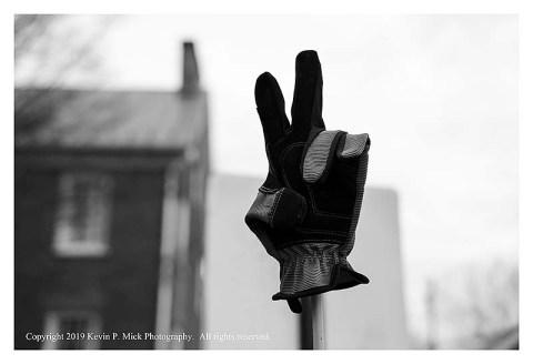BW photograph of a lost glove atop a post posed in a peace sign.