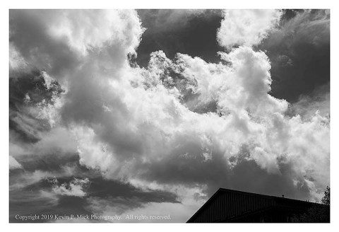 BW photograph of clouds over a silhouetted building.