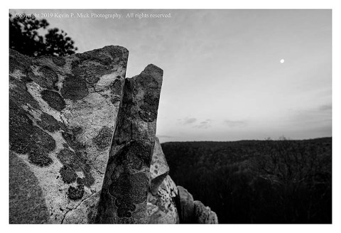 BW photograph of the moon setting in the background with a rock formation in the foreground.