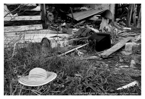 BW photograph of a hat outside of a destroyed house in New Orleans post Katrina.