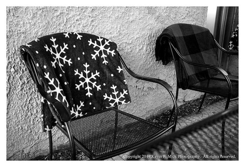BW photograph of chairs with blankets outside of a coffee shop on a chilly morning.