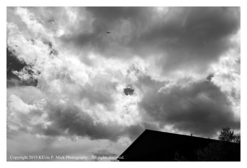 BW photograph of a plane flying into a cloud bank.