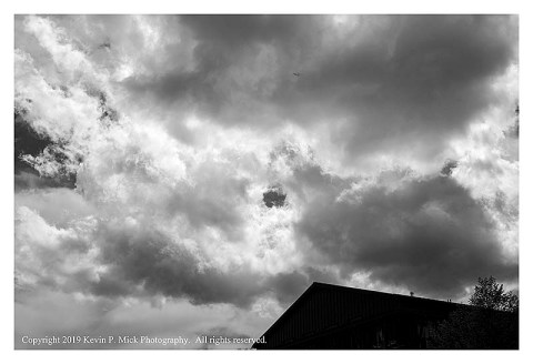 BW photograph a plane flying into a cloud bank.