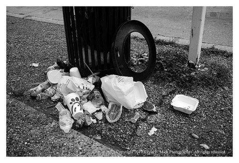 BW photograph of food trash laying at the base of a trash can.