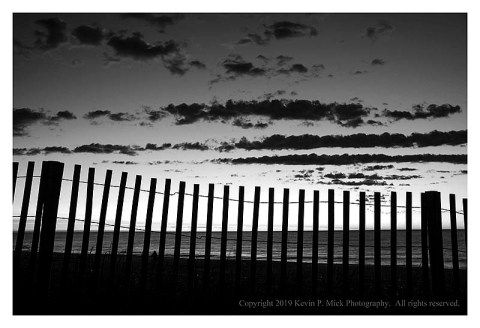 BW photograph of the sunrise behind a dune fence.