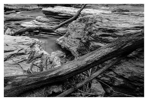 BW photograph of logs among the rocks at Morgan Run after the flood.